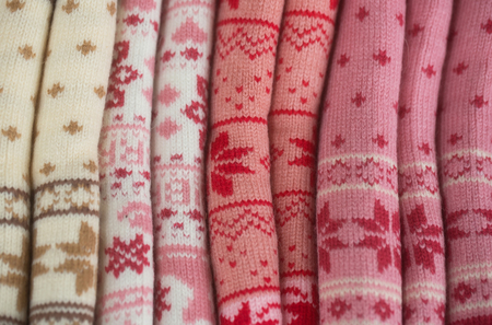 Knits or knitted collection with snowflake pattern rolled on colorful woolen background. Knitting and knitwear. Fashion. Warm winter clothes