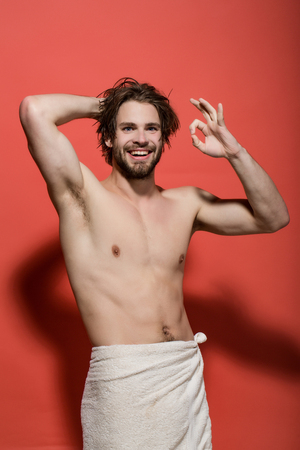 morning wake up and shower of happy man with beard and long hair in white towel on red background showing ok gesture