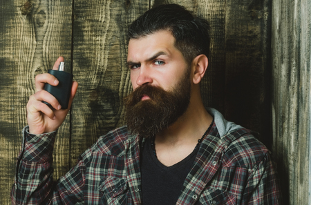 perfume. Brutal man or bearded caucasian hipster with grey hair, long beard and moustache applying cologne from black bottle on wooden background. Male fragrance and perfumery. Cosmetics Reklamní fotografie