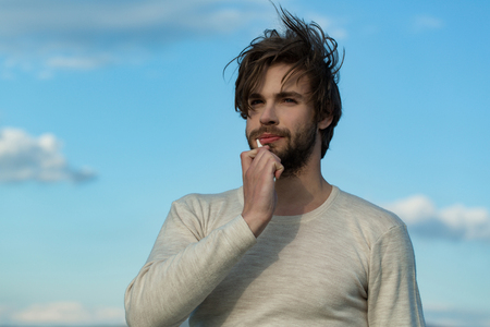 man brush teeth with toothpaste, has beard and hair in underwear on blue sky background morning outdoor, hygiene and spa, metrosexual
