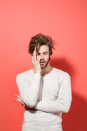 sleepy man with disheveled and uncombed long hair and closed eyes, with beard on face in white underwear on red background, morning and wake up, everyday life, barbershop Stock Photo