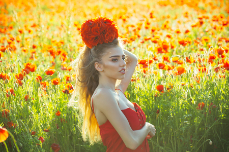poppy seed bouquet at girl with long curly hair in red dress in flower field with green stem on natural background, summer, spring, drug and love intoxication, opium Stock Photo