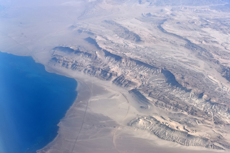Aerial view on coast where rugged barren dunes of desert meet with blue ocean, beautiful natural landscape outdoor, summer vacations concept