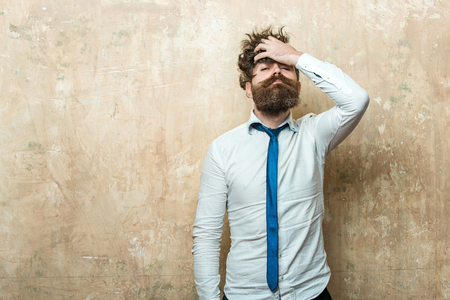 man or hipster with long beard and raised hand on stylish hair on serious face in tie and white shirt on textured beige background, copy space