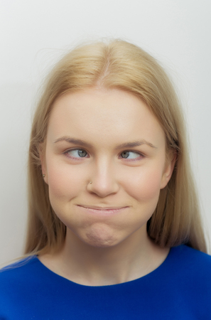 Woman squinting eyes and puffing cheeks on funny face. Cute girl with crossed grey eyes, healthy skin and long blond hair in blue dress on white background. Grimace and facial expression. Strabismus