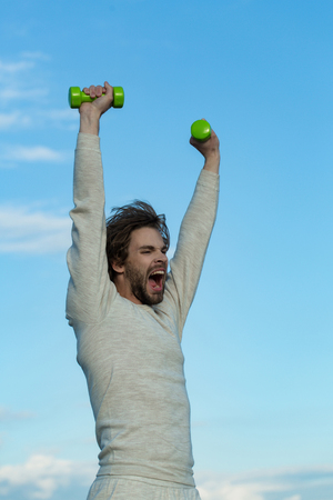 morning exercise of man with barbell or dumbbell workout, has disheveled and uncombed long hair and beard on yawning face in white underwear on blue sky background, wake up, sport and health Imagens