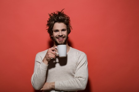 happy man with cup of tea or coffee has uncombed hair in underwear on red background, morning refreshment and drink, energy, copy space Stock Photo