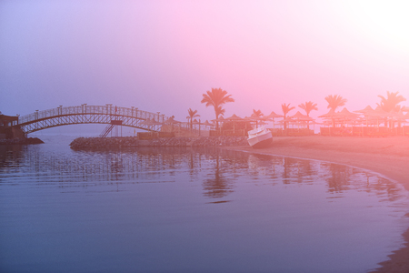 Evening landscape with pink and blue sky palm trees empty cafe and white boat at coast of ocean, summertime traveling, recreation and vacation concept Stock Photo