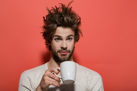 morning refreshment of surprised man with cup of tea or coffee has uncombed hair in underwear on red background, and drink, energy