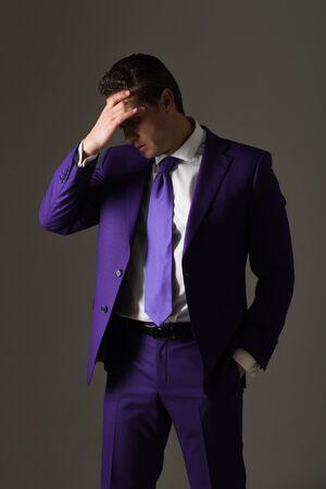 実業家、男やスタイリッシュな髪、正式なファッショナブルなバイオレットで散髪のボス感頭痛スーツ、白いシャツと灰色の背景にネクタイします