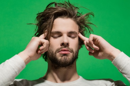 headache. tired guy or handsome man with beard and stylish hair in white underwear on green background, morning and fashion Stock Photo