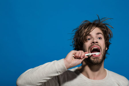 man brush teeth with toothpaste on blue background, copy space