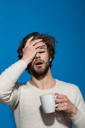 sleepy tired man with headache hold cup of tea or coffee has uncombed hair in underwear on blue background, morning refreshment and drink