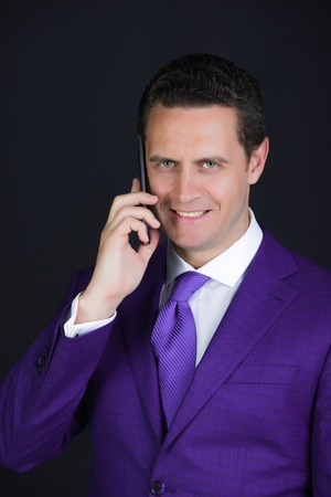 man smiling and talking on smartphone or mobile phone in violet suit and tie on grey background. Technology for business. Digital marketing, internet surfing and information Stock Photo