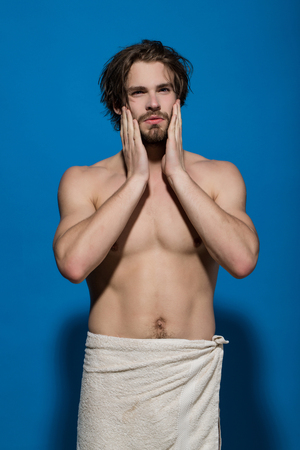man or guy with towel has bare muscular torso and beard hold hands at face on blue background in morning Stock Photo