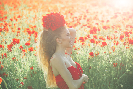 woman or happy smiling girl with long curly hair in red dress hold flower bouquet in field of poppy seed with green stem on natural background, summer, spring, drug and love intoxication, opium Stock Photo