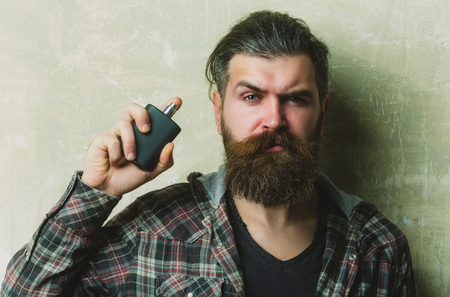 man or brutal caucasian hipster with grey hair, long beard and moustache posing with black perfume or cologne bottle on cement wall. Male fragrance and perfumery. Cosmetics Reklamní fotografie