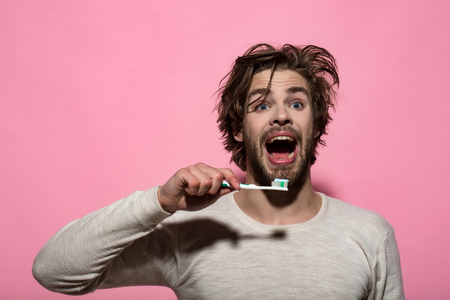 toothpaste on teeth brush at happy man in underwear on pink background, morning hygiene and dental health Stock Photo
