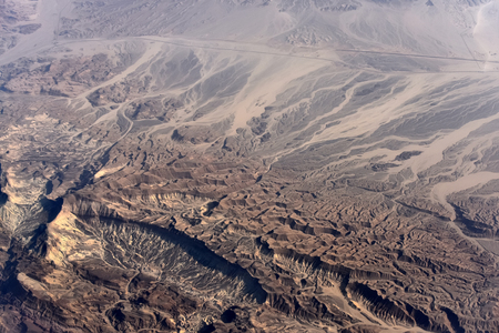 Aerial view of desert with hilly rugged terrains from airplane flight on natural background