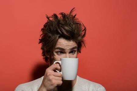 Homme avec une tasse. Rafraîchissement du matin d'un homme surpris avec une tasse de thé ou de café avec des cheveux sans peigne en sous-vêtements sur fond rouge et une boisson, de l'énergie Banque d'images - 81716266
