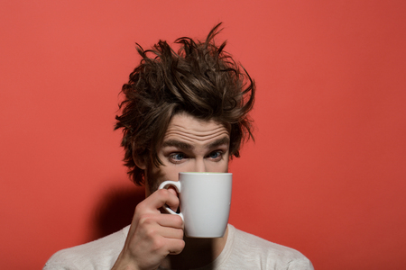 man with cup. morning refreshment of surprised man with cup of tea or coffee has uncombed hair in underwear on red background, and drink, energy