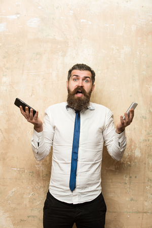 businessman or bearded man with long beard and stylish hair on surprised face in tie and white shirt on beige background compare mobile phone and smartphone, conversation and information