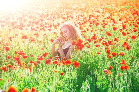 young girl in a poppy field with mobile phone on natural summer background Stock Photo