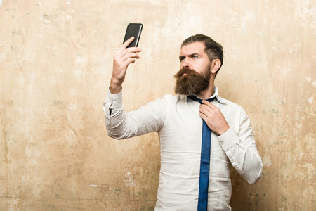 man with long beard and stylish hair in tie and white shirt on beige background make selfie on mobile phone, conversation and information, businessman Stock Photo