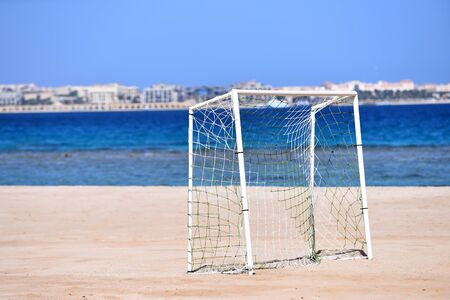 Goal soccer with white net on sand beach on background of blue sea and sky in summer outdoor.