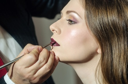 professional makeup artist working with beautiful young woman, skincare and cosmetics, fashion victim
