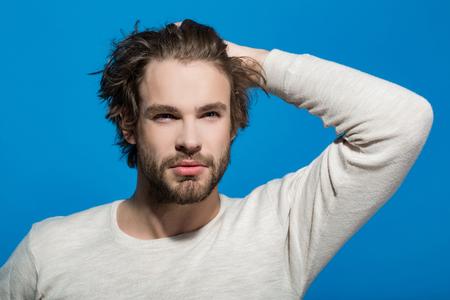Bel homme à la barbe et aux cheveux élégants en sous-vêtements blancs avec la main sur le fond bleu, le matin et la mode Banque d'images - 81716346