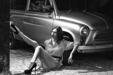 young girl on road near beautiful retro car, black and white vintage style