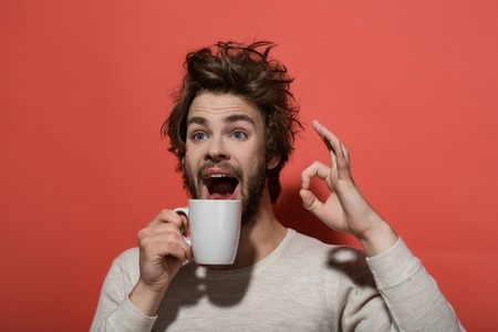ok gesture of surprised man with cup of tea or coffee has uncombed hair in underwear on red background, morning refreshment and drink, energy Stock Photo
