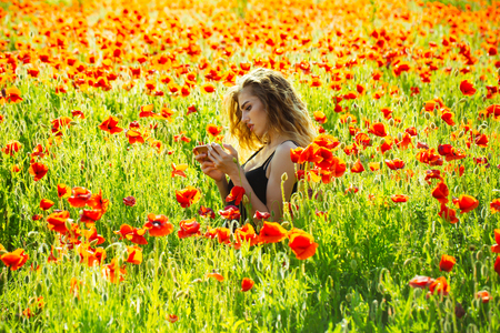 infatuation: girl in flowers. woman hold mobile phone in field of red poppy seed with green stem on natural background, summer, spring, drug and love intoxication, opium, new technology