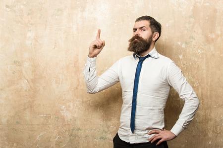 man of hipster met lange baard en stijlvolle haren op ernstig gezicht in stropdas en wit overhemd op gestructureerde beige achtergrond met opgeheven vinger, kopie ruimte