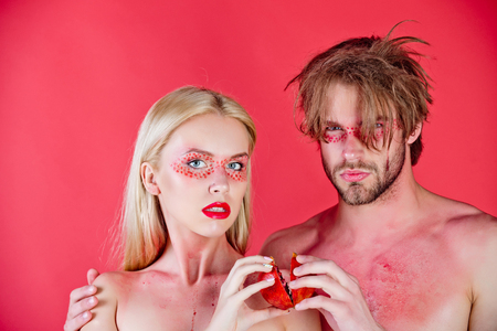 young couple of woman and man with creative fashionable makeup on face hold pomegranate fruit on red background, beauty and fashion, allergy, healthcare and vitamin, vegetarian and dieting, hemoglobin
