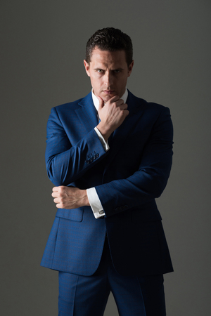 Thoughtful man, businessman or manager with serious face and stylish hair, haircut posing in fashionable blue formal suit on grey background. Business, fashion and success Фото со стока
