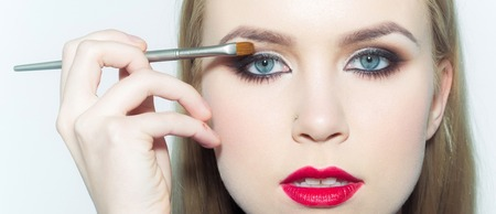 Girl with red lips applying eyeshadows on eyelids with makeup brush. Woman face with blue eyes and healthy young skin isolated on white. Beauty salon. Visage and make up. Cosmetics and skincare