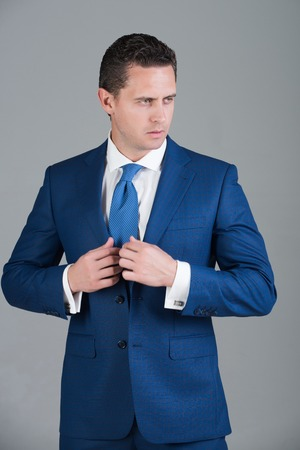 男は、自信を持っているビジネスマンやスタイリッシュな髪、灰色の背景にネクタイでおしゃれなフォーマルなスーツでポーズ散髪マネージャーが