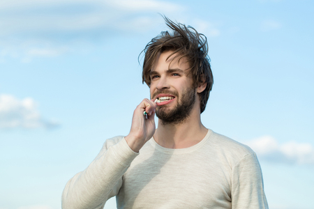 happy handsome man brush teeth with toothpaste, has beard and hair in underwear on blue sky background morning outdoor, hygiene and spa, metrosexual