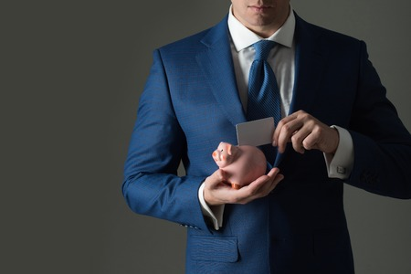 Stylish formal blue suit and tie. Male hands putting blank business card in piggy bank for saving on grey background. Banking, money, loan, moneybox, ecash and information Stok Fotoğraf