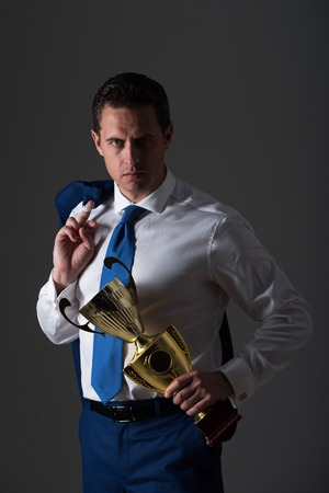 man champion, confident businessman or manager holding golden winner cup in fashion white shirt, blue tie and jacket on shoulder on grey background. Business and success. Victory and trophy Imagens