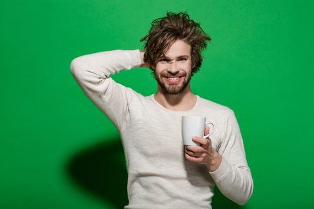 morning refreshment of happy man with cup of tea or coffee has uncombed hair in underwear on green background, and drink, energy