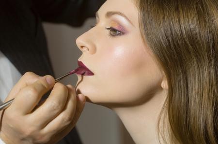 Belleza y moda. Visagiste poner lápiz labial con cepillo. Mujer linda o muchacha bonita con la piel sana joven de la cara y el maquillaje con estilo que consigue los labios pintados en salón de belleza. Visage, cosméticos