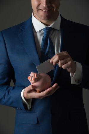 handen die leeg adreskaartje in spaarvarken voor besparing op grijze achtergrond zetten. Stijlvol formeel blauw pak en stropdas. Bankieren, geld, lening, spaarpot, ecash en informatie Stockfoto
