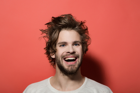happy man with long stylish uncombed hair and smiling bearded man on red background, morning and barbershop fashion