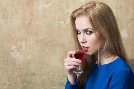 Girl drinking red liqueur in glass. Woman with blond long hair, make up in blue dress on beige wall. Alcohol, appetizer, bad habits, addictive and convive. Unhealthy lifestyle, copy space