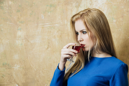 Girl in blue dress drinking red liqueur in glass. Woman with blond long hair and make up on beige wall. Alcohol, appetizer, bad habits, addictive and convive. Unhealthy lifestyle, copy space