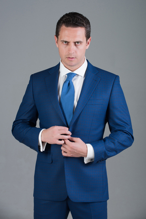 Handsome man, confident businessman or successful boss with stylish hair, haircut buttoning button on elegant blue formal suit jacket on grey background. Business, fashion and success. Dress code