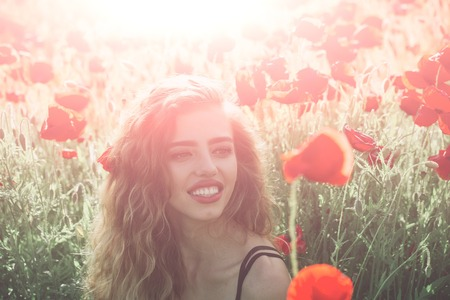 girl with long curly hair hold flower in field of red poppy seed with green stem on natural background, summer, spring, drug and love intoxication, opium